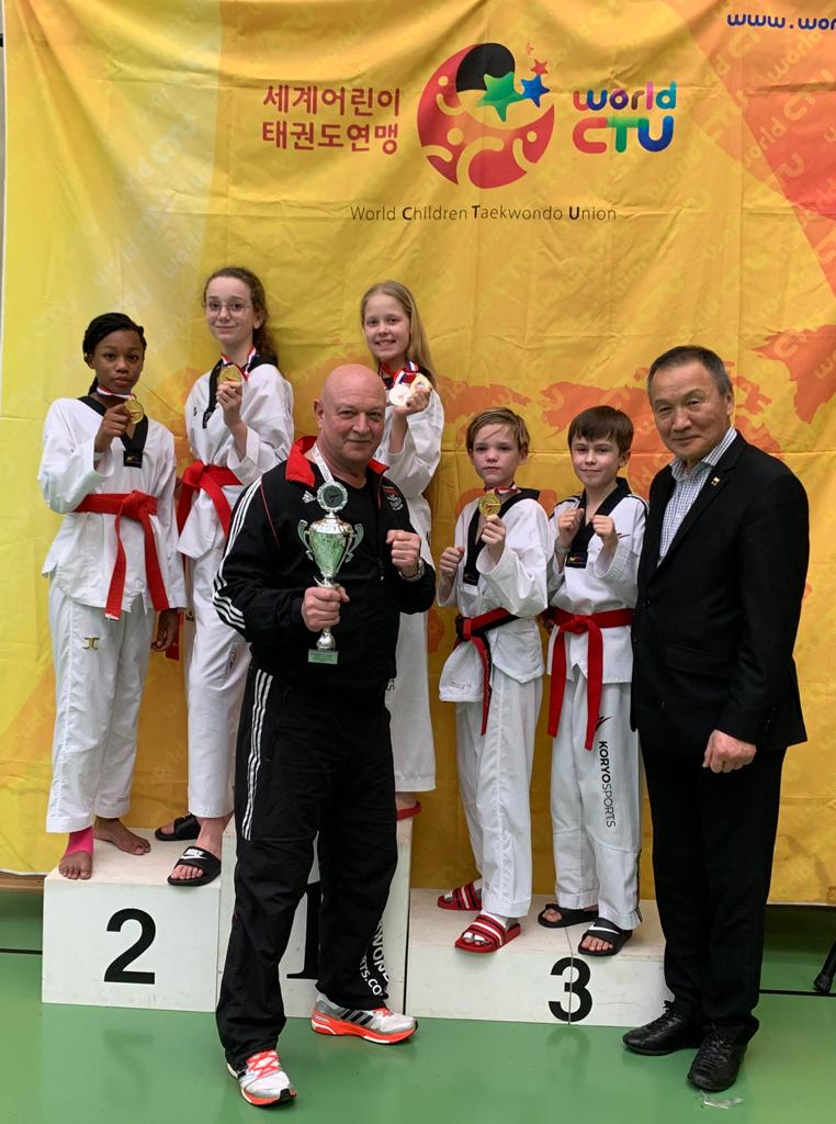 Op het Podium Lhaekeysha Martijn, Eva Moors, Nielle Vroegh, Joep van Limpt, Jordhi Wyrwa. Op de voorgrond Trainer Anthony Wijnhoven en Dr. Soo-Nam,Park,  President of World Children Taekwondo Union  President DTU (Deutsche Taekwondo Union)
